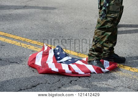 Saint Louis, MO, USA - March 11, 2016: Protester desecrates flag outside a Donald Trump rally in the Peabody Opera House in Downtown Saint Louis