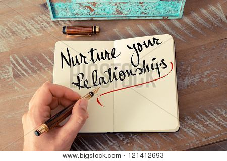 Retro effect and toned image of a woman hand writing a note with a fountain pen on a notebook. Handwritten text Nurture Your Relationships as business concept image
