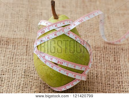 Pear With Meter On The Brown Background, Front View