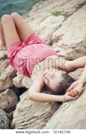 Beautiful young woman posing on stones near sea