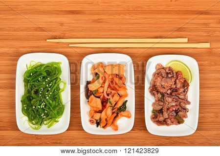 Three Seafood Salads With Chopsticks On Wood