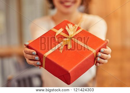Cheerful woman giving present