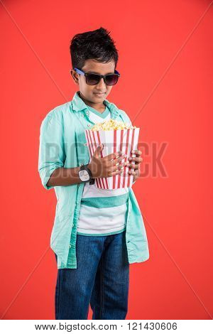 Joyful indian kid holding a big box of popcorn isolated on red background