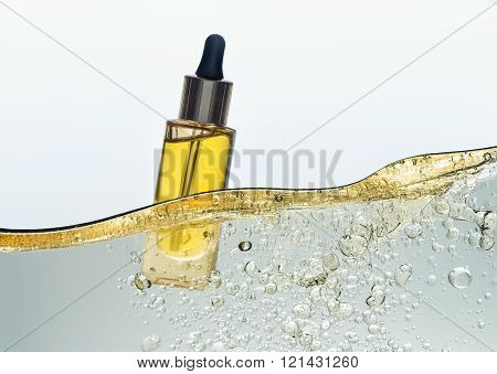 The bottle of the yellow cosmetic oil in the oil emulsion wave
