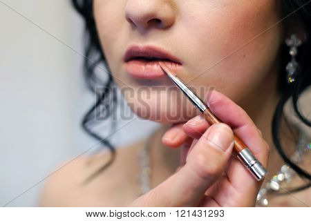 Lip makeup for girls. The color of the lips lipstick. Beautiful woman applying lipstick. Makeup to plump lips. Cosmetics for the mouth. ** Note: Shallow depth of field