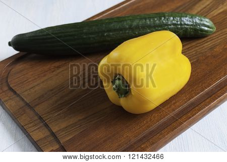Cutting Board With Yellow Pepper And Green Cucumber