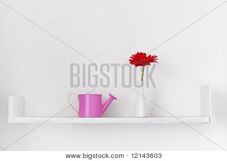Decorative shelf on white wall with flower ina vase on it