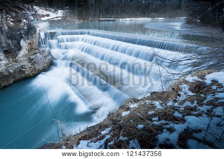 flowing water over steps of river fall at winter in bavaria