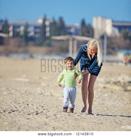 Young mother with her kid resting at the beach