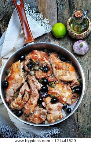 Roast rabbit in white wine with rosemary, olives and capers