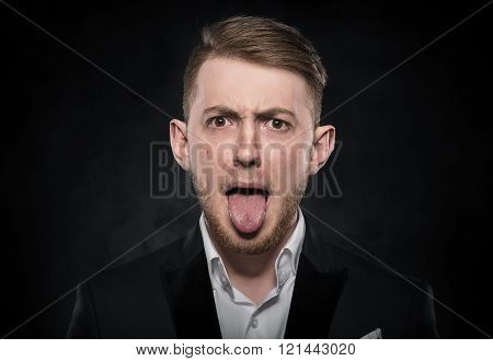 Young businessman with tongue out.