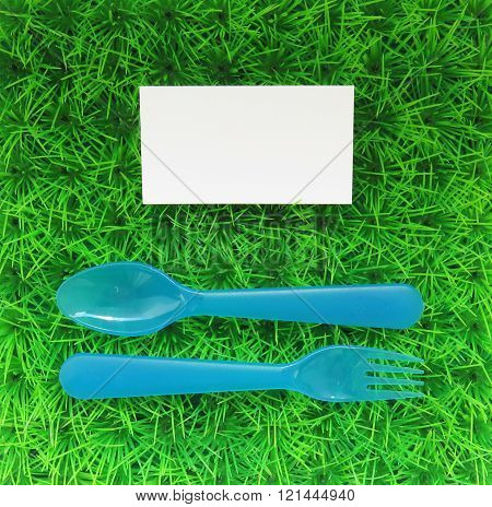 Plastic Fork And Spoon On A Green Lawn With A Business Card Top View
