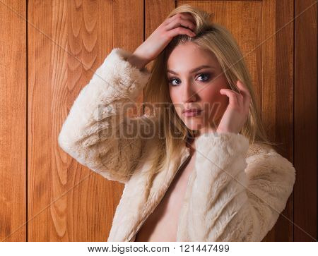 Young beautiful blonde sexy girl in wool coat standing in front of old locker, retro look, 70s style