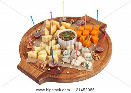 Cheeseboard On Serving Round Wooden Plate Isolated On White Background.