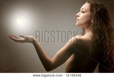 a portrait of a beautiful  woman with a light on the hand