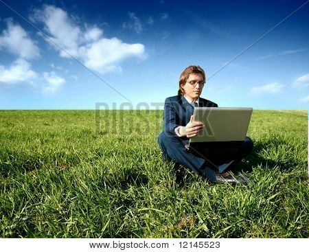 a young business man with a laptop on the grass field