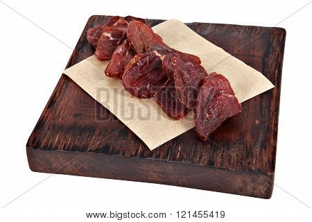 Slices Of Dried Meat On Serving Dark Brown Board Isolated.