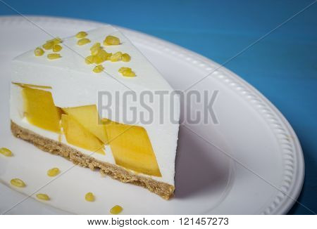 Close Up Of Mango Cream Pie With Peeled Split Mung Bean On White Plate And Blue Wood ,vintage Toning