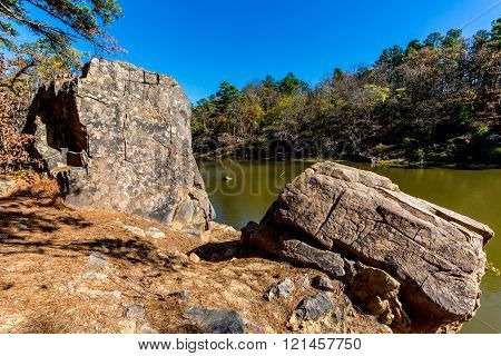 A Tranquil Autumn Outdoor Scene with Huge Boulders on Ash Creek at Robbers Cave State Park in Oklahoma.