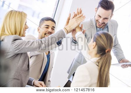 Shot of a group of colleagues high-fiving each other during an informal meeting.Happy business team celebrating good news.