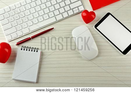 Computer peripherals with red hearts, notebook and mobile phone on light wooden table
