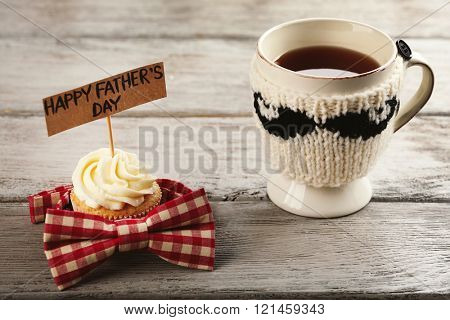 Happy fathers day special cupcake, cup of tea and bow tie on wooden table