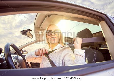Young woman is drawing her car.She is enjoying driving car on sunny day at the city.