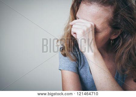 One Sad Woman Sitting Near A Wall