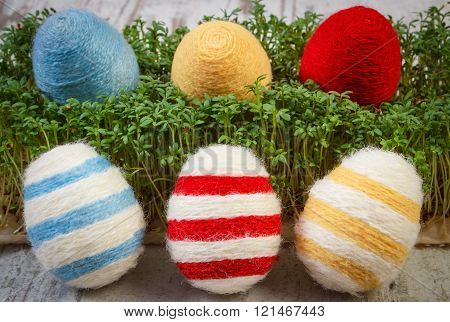 Easter Eggs Wrapped Woolen String And Green Cress On Wooden Background, Decoration For Easter