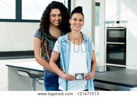 Pregnant lesbian couple holding a sonography report and smiling in kitchen