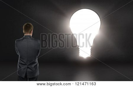 Businessman standing in front of bright big idea light bulb looking like a door
