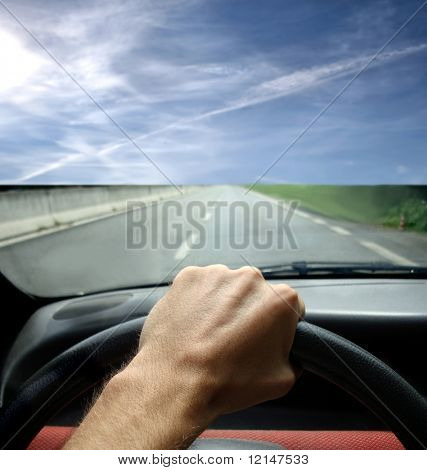 a closeup of steering wheel and a hand of a man in a car