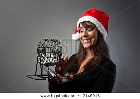 beautiful  young woman wearing santa claus hat with a bingo