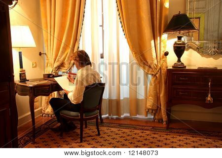 a man  write in  a luxury hotel room