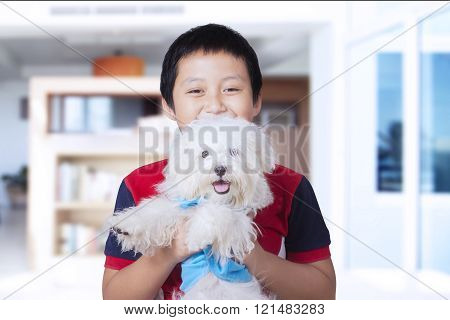 Cheerful boy holds maltese dog at home