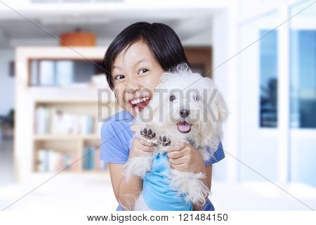 Happy Little Girl And Maltese Dog At Home