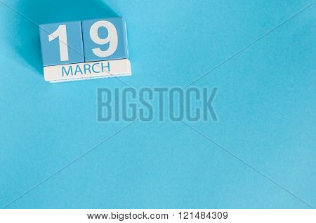 March 19th. Image of march 19 wooden color calendar with flower on blue background.  Spring day. Ear