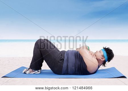 Overweight Man Doing Workout At Coast