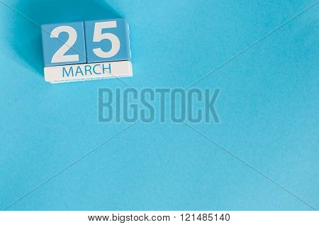 March 25th. Image of march 25 wooden color calendar on blue background.  Spring day, empty space for