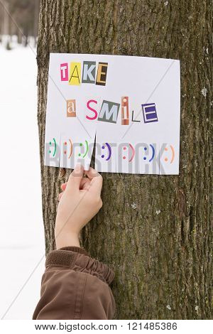 Human hand keeps for paper ad with the phrase: Take a Smile and with smile signs ready to be tore of