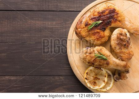 Grilled chicken lag and chicken drumstick on wooden background.