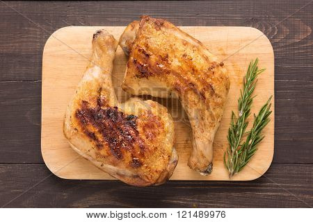 Grilled chicken lag and rosemary on wooden background.