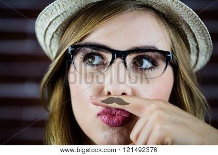 Pretty blonde woman doing a moustache with her finger on brick wall background