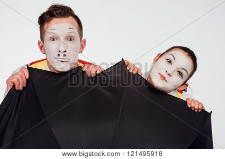 studio shot of two mimes isolated on a white background. with umbrella