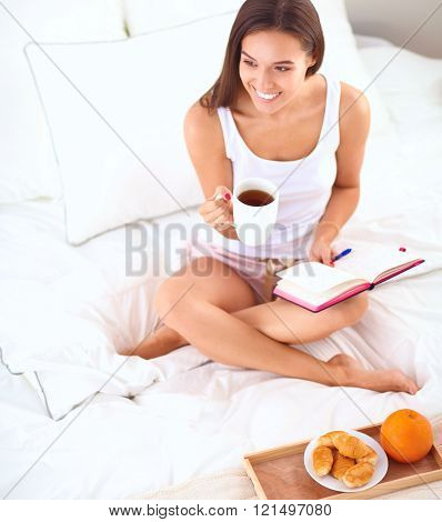 Young beautiful woman sitting in bed and writing in a copybook