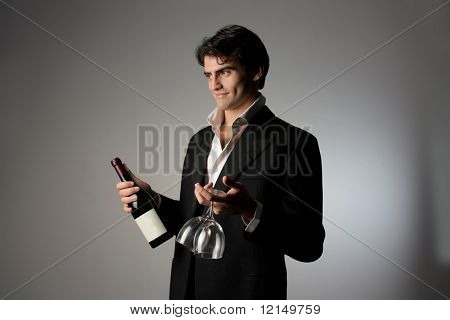 young beautiful man with a bottle of wine and glass
