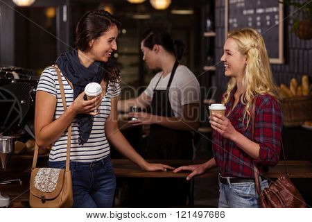 Smiling friends enjoying coffee at the coffee shop