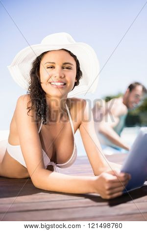 Portrait of happy woman in hat using digital tablet by pool side on a sunny day