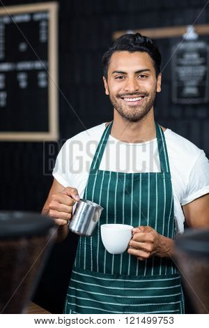 Handsome waiter serving coffee cup at the coffee shop