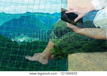 Man Use Tablet While Relaxing Beside Water Pool With Scenic Of City In Mountain Or Valley